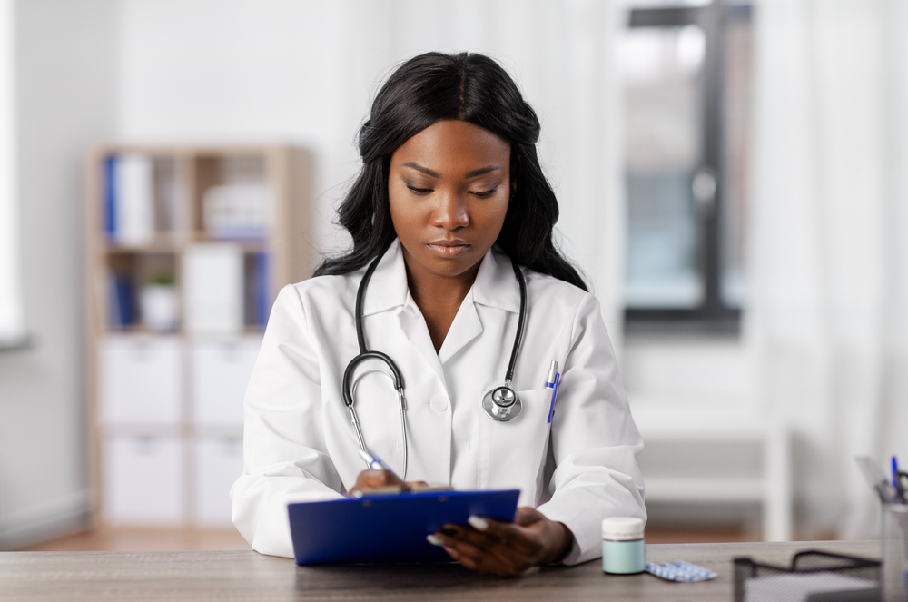 black woman doctor on tablet